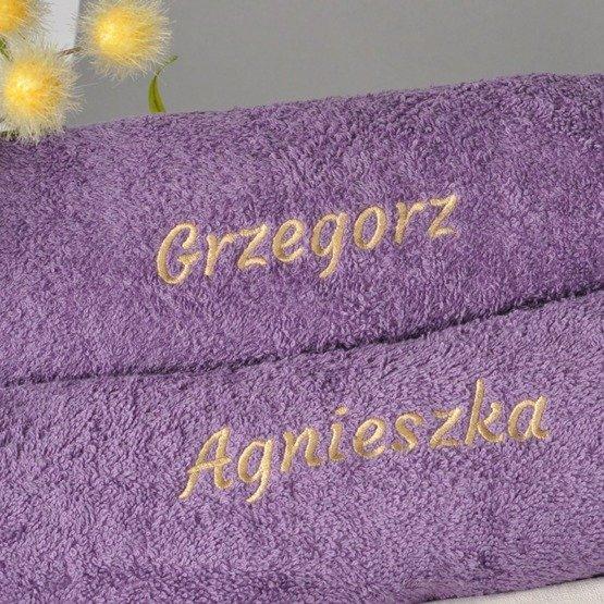 Dwa fioletowe ręczniki kąpielowe z imionami, w koszyku